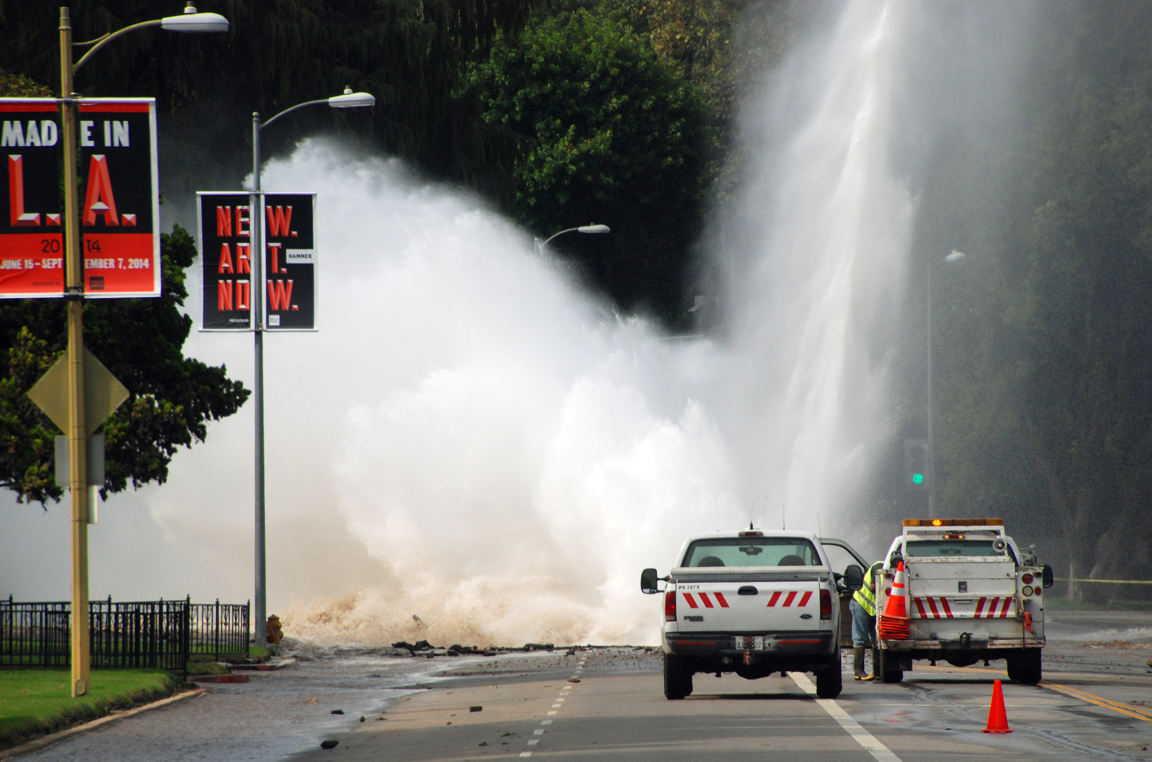 Water shoots in the air from a broken 30-inch water main under Sunset Boulevard, uphill from UCLA in the Westwood section of Los Angeles, Tuesday, July 29, 2014. The resulting flood inundated several areas of UCLA, including Pauley Pavilion, home of UCLA basketball, a parking structure and several other building. (AP Photo/Mike Meadows)